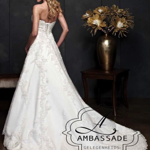 achterkant van vrouw in kanten A-lijn bruidsjurk met rijgveter sluiting en lange sleep.