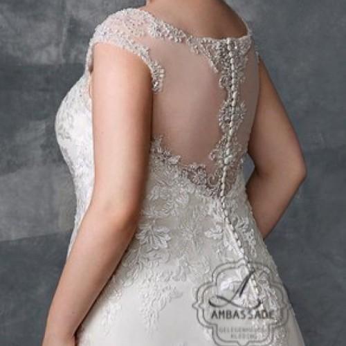 Detail van achterkant van bruidsjurk met transparante, lage rug die sluit met knoopjes.