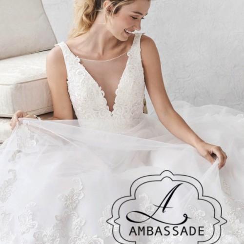 Zittende vrouw in bruidsjurk met kanten lijfje met diep decolleté en tule rok.