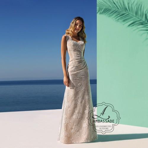 Voorkant van vrouw in slanke, kanten bruidsjurk op strand.