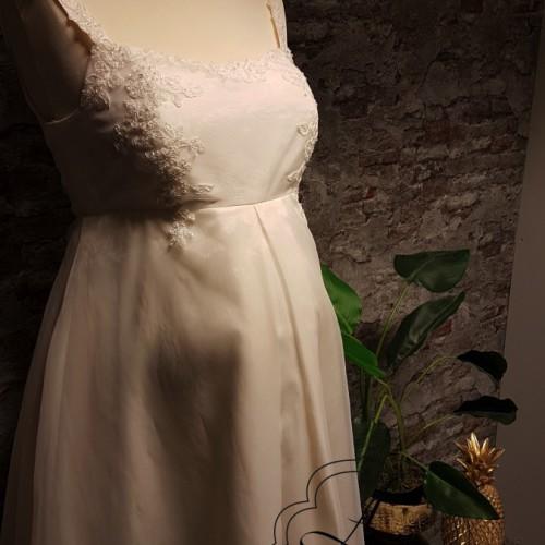 Voorkant van positie bruidsjurk voor een zwangere bruid met bandjes.