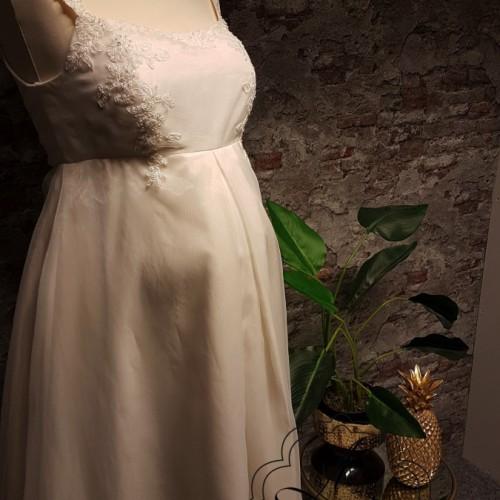 zijkant van positie bruidsjurk met zwangere buik op pop.