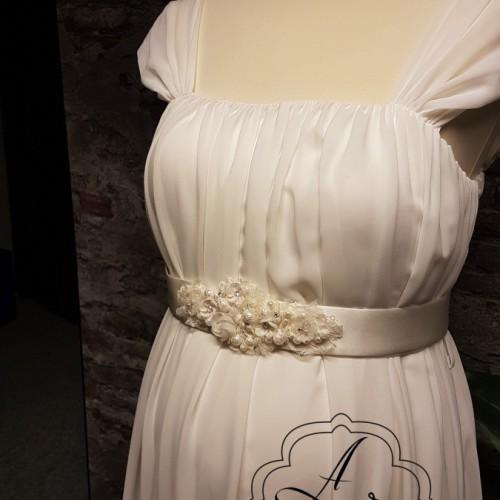 Detail van positie bruidsjurk van chiffon met mouwtje en zwangere buik.