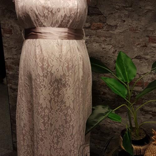 Kanten positie bruidsjurk met roze accenten en tailleband.