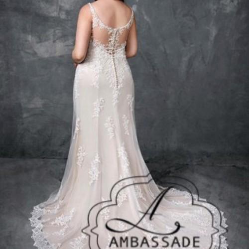 Achterkant van dame met grote maat in kanten bruidsjurk met semi transparante rug en sleep.
